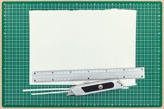 Papierblatt mit Metallmachthaber und Hilfsmesser auf grünem Ausschnitt Stockbild