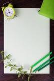 Papierblatt, Uhr, Bleistifte und Minze auf dunklem hölzernem Hintergrund Stockbild