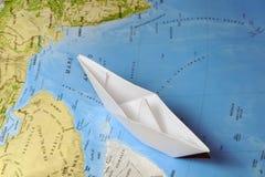 Papierboot auf einer Karte Lizenzfreie Stockfotografie