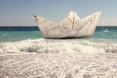 Papierboot, das in ein Meer schwimmt Stockbild