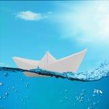 Papierboot, das unter den Wellen im Ozean schwimmt Lizenzfreie Stockfotografie