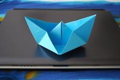 Papierbootssegeln auf Laptop Stockfoto