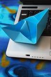 Papierbootssegeln auf Laptop Lizenzfreie Stockfotos