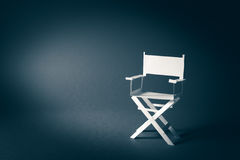 Papierdirektornstuhl auf einem bläulichen grauen Hintergrund Stockbilder