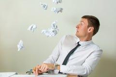 Papiere, die in junges Geschäftsmanngesicht fliegen Stockfotos