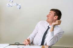 Papiere, die in junges Geschäftsmanngesicht fliegen Stockbilder