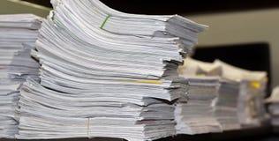 Papiere gestapelt auf einem Schreibtisch lizenzfreie stockfotografie