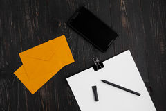 Papiere mit Stift und Umschlägen und zelluläres auf hölzernem Hintergrund Stockfotografie
