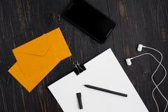 Papiere mit Stift und Umschlägen und zelluläres mit Kopfhörern auf hölzernem Hintergrund Lizenzfreies Stockbild