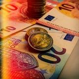 Papiereurobanknoten und Münzen Die Münze ist zwei Euros Lizenzfreies Stockfoto
