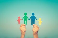 Papierfamilie in den Händen Stockfoto