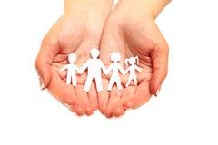 Papierfamilie in den Händen Stockfotografie