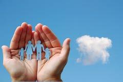Papierfamilie in den Händen auf Hintergrundwohlfahrtskonzept des blauen Himmels Stockfotografie