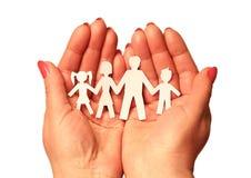 Papierfamilie in den Händen auf weißem Hintergrund Lizenzfreies Stockfoto