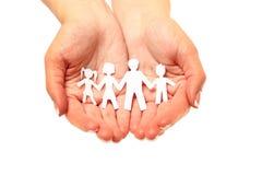 Papierfamilie in den Händen lokalisiert auf weißem Hintergrund Stockfotografie