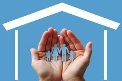 Papierfamilie in den Händen mit Haus auf blauem Hintergrundwohlfahrtskonzept Lizenzfreie Stockbilder