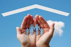 Papierfamilie in den Händen mit Haus auf Hintergrund des blauen Himmels lizenzfreies stockfoto