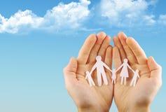 Papierfamilie in den Händen Lizenzfreie Stockfotos