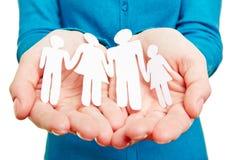 Papierfamilie in den weiblichen Händen Lizenzfreie Stockbilder