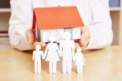 Papierfamilie mit Haus Stockfotografie