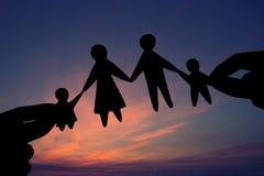Papierfamilie in zwei Händen gegen den Himmelhintergrund lizenzfreie stockfotos