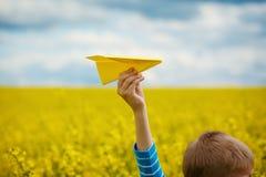 Papierflugzeug in den Kinderhänden auf gelbem Hintergrund und blauem s Stockfotografie