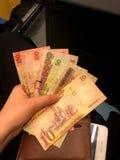 Papiergeld in den H?nden eines jungen M?dchens Banknoten von Saudi-Arabien lizenzfreie stockfotos