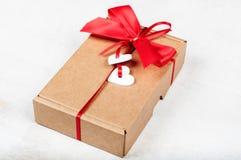 Papiergeschenkbox mit rotem Bogen und weiße hölzerne Herzen für Valentin Stockfoto