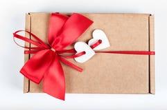 Papiergeschenkbox mit rotem Bogen und weiße hölzerne Herzen für Valentin Lizenzfreie Stockfotos