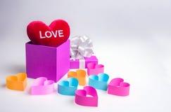 Papiergeschenkbox und Herzen auf weißem Hintergrund Stockfoto