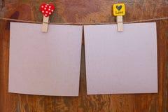 Papierhängen von einem Seil auf einem hölzernen Hintergrund Lizenzfreie Stockfotografie