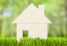 Papierhaus auf grünem Gras. Hypothekenkonzept. Stockbild
