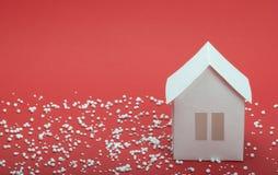 Papierhaus im Schnee auf rotem Hintergrund Stockbild