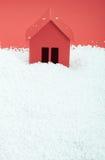 Papierhaus im Schnee auf rotem Hintergrund Stockbilder