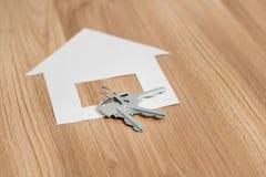 Papierhaus mit einem Schlüssel von der neuen Wohnung lizenzfreie stockfotos