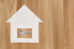 Papierhaus mit einem Schlüssel von der neuen Wohnung stockbild