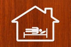 Papierhaus mit schlafendem Mann auf Bett mit copyspace Lizenzfreie Stockfotos