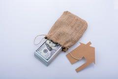 Papierhaus neben US-Dollar Banknote Stockfotos