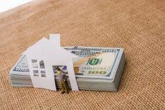 Papierhaus und eine Mannfigürchen neben US-Dollar Banknote Lizenzfreie Stockbilder