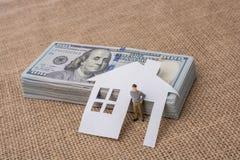 Papierhaus und eine Mannfigürchen neben US-Dollar Banknote Stockbilder