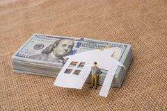 Papierhaus und eine Mannfigürchen neben US-Dollar Banknote Stockfotografie