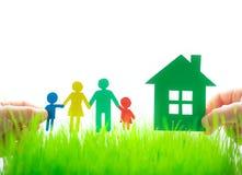 Papierhaus und Familie in den Händen Stockfotos