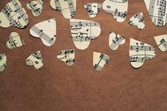 Papierherzen mit Musikanmerkungen über Kraftpapier Stockbilder