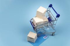 Papierkästen in einer Laufkatze auf blauem Hintergrund Konzept: Lieferung, on-line-Einkaufen stockfotos