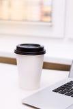 Papierkaffeetasse auf dem Tisch und Laptop Stockfoto