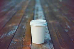 Papierkaffeetasse am Holztisch lizenzfreie stockbilder