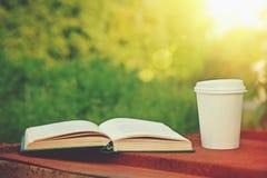 Papierkaffeetasse und Buch lizenzfreie stockfotografie