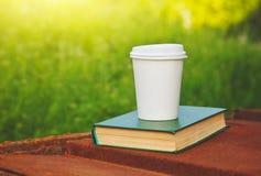 Papierkaffeetasse und Buch stockbild