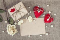 Papierkarte mit Geschenkbox, Weißrose, Herzen und Perlenperlen Lizenzfreie Stockfotos