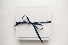 Papierkasten des einzelnen weißen Geschenks mit dem Bogen des blauen Bandes, lokalisiert auf weißem Hintergrund Stockbild